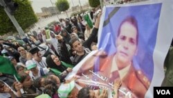 Pendukung Gaddafi menghadiri pemakaman putera Gaddafi di Tripoli (2/5), sambil membawa poster seorang Kolonel Libya yang terbunuh dalam serangan NATO bulan April lalu.