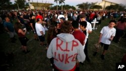 """Zachary Haupert, 14, painted """"RIP Luke,"""" on his hoodie in honor of his friend Luke Hoyer, who was one of the victims of the shooting at Marjory Stoneman Douglas High School, as he attends a candlelight vigil, Feb. 15, 2018, in Parkland, Florida."""