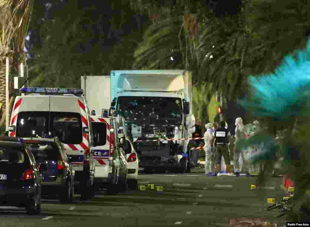 Pasukan polisi Perancis dan petugas forensik berdiri dekat truk yang menabrak kerumunan massa di Nice, Perancis (15/7). (Reuters/Eric Gaillard)