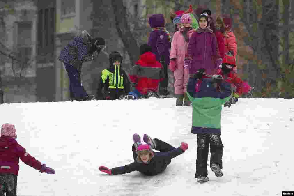 نیو یارک کے علاقے مین ہیٹن میں ایک پارک میں برف جمع ہے جب کہ بچے برف پر کھیل رہے ہیں