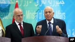 Iraqi Foreign Minister Ibrahim al-Jaafari, left, listens to Arab League Secretary-General Nabil Elaraby during a news conference in Baghdad, Iraq, Sunday, Oct. 19, 2014.
