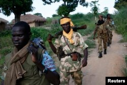 FILE - Seleka fighters patrol the town of Lioto, Central African Republic, June 6, 2014.