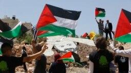 Para aktivis Palestina berdema dekat instalasi militer Israel di Kota Ramallah, Tepi Barat, 9 Mei 2017.