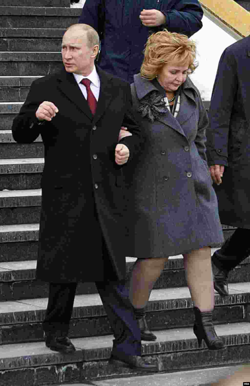 Russian Prime Minister and presidential candidate Vladimir Putin and his wife Lyudmila leave a polling station in Moscow, Russia, March 4, 2012. (AP)