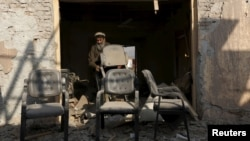 Afghan man removes broken chairs from his shop near the site of a suicide car bomb attack in Surkhrod district of Nangarhar province, Dec. 7, 2015.