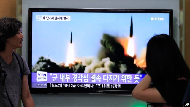 FILE - South Koreans watch a TV news program showing a missile launch by North Korea, at Seoul Railway Station, Seoul, June 26, 2014.