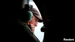 Một thành viên phi hành đoàn nhìn ra từ cửa sổ của máy bay trinh sát AP-3C Orion trong cuộc tìm kiếm chuyến bay MH370 ở Ấn Độ Dương, ngày 26/3/2014.