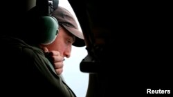 A crew member looks out an observation window from a Royal Australian Air Force (RAAF) AP-3C Orion aircraft while searching for the missing Malaysia Airlines Flight MH370 over the southern Indian Ocean, March 26, 2014.