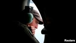 一架在印度洋南部上空搜索失踪马航班机残骸的澳大利亚皇家空军AP-3C猎户座飞机上的机组人员透过机窗查看海面。(2014年3月26日)