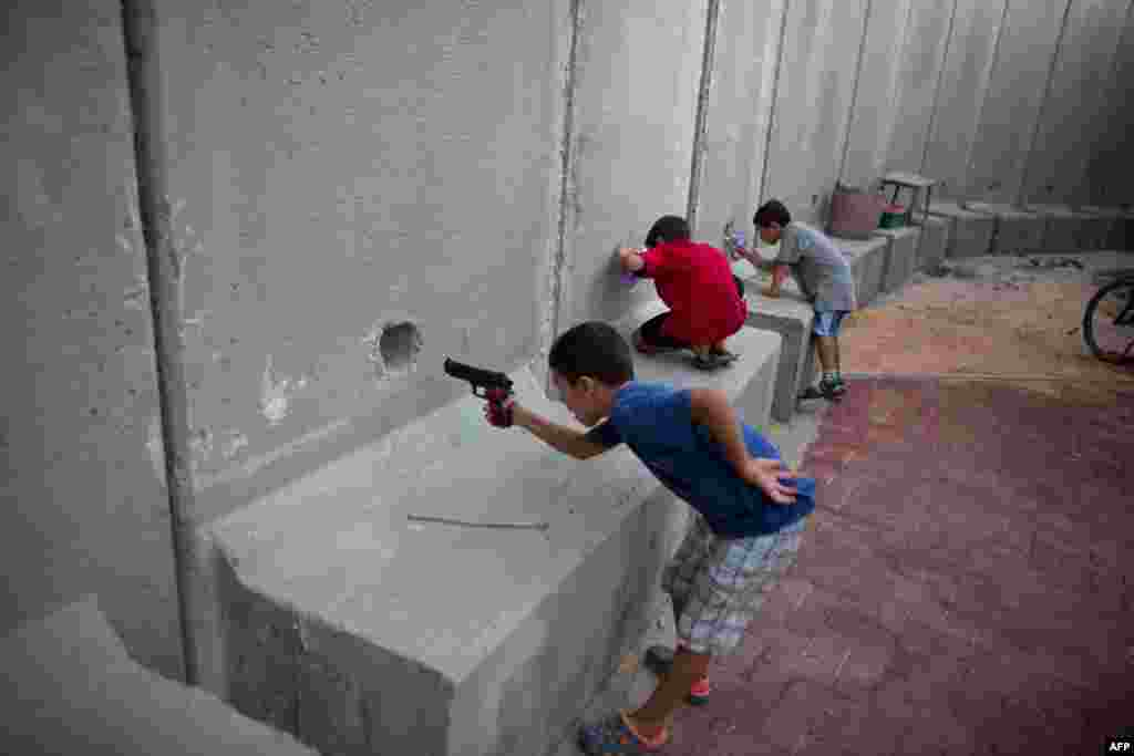 Israeli children hold toy guns as they pretend to play war games next to newly built protection cement walls around a kindergarten in the center of Kibbutz Nahal Oz located near the border with Gaza Strip.