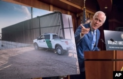 FILE - Senate Majority Whip John Cornyn of Texas points to a poster as he talks to reporters about border security on Capitol Hill, Washington, Aug. 3, 2017.