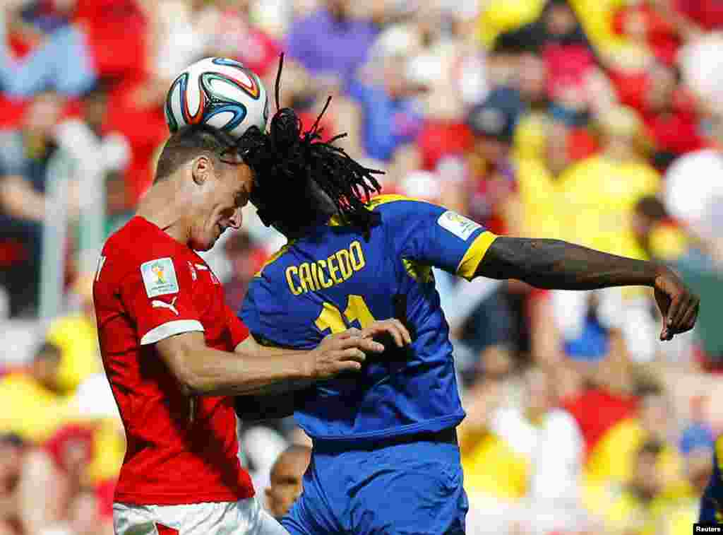 Switzerland's Steve von Bergen fights for the ball with Ecuador's Felipe Caicedo (R) during their 2014 World Cup Group E soccer match at the Brasilia national stadium in Brasilia, Brazil.