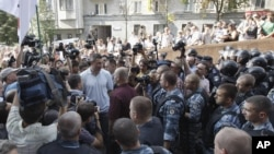WBC Heavyweight Champion Vitali Klitschko, center in white t-shirt, talks to riot police at an opposition protest rally in front of the Ukrainian House in central Kiev, Ukraine, July 4, 2012.