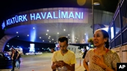 People gather at the entrance to Istanbul's Ataturk airport in the early-morning hours of June 29, 2016, after suicide bombers struck in the terminal, killing dozens of people and wounding many others.