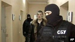 """俄罗斯电视网""""一频道""""报道中显示,乌克兰安全局蒙面特工押送暗杀普京嫌疑人(中)"""