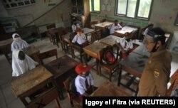 Para pelajar dan guru memakai masker setelah pemerintah Indonesia membuka kembali kegiatan belajar tatap mukadi tengah pandemi COVID-19 di Pariaman, Provinsi Sumatera Barat, 13 Juli 2020. (Foto: Antara /Iggoy el Fitra/via Reuters)
