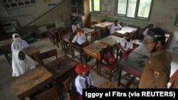 Siswa dan guru memakai masker pelindung setelah pemerintah Indonesia membuka kembali sekolah dengan menerapkan proses pembelajaran tatap muka di tengah wabah Covid-19 di Pariaman, Provinsi Sumatera Barat, 13 Juli 2020. (Foto: Antar /Iggoy el Fitra/via Reu