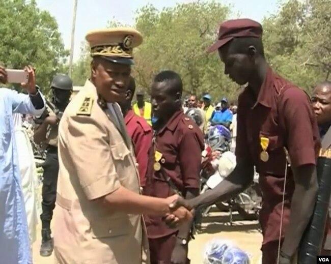 The Governor of Cameroon's far north region Midjiyawa Bakari greets a vigilante member. (M.E. Kindzeka/ VOA)