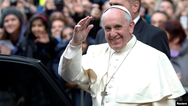 Pope Francis waves as he leaves at the end of his mass at the Church of the Most Holy Name of Jesus in Rome, Jan. 3, 2014.