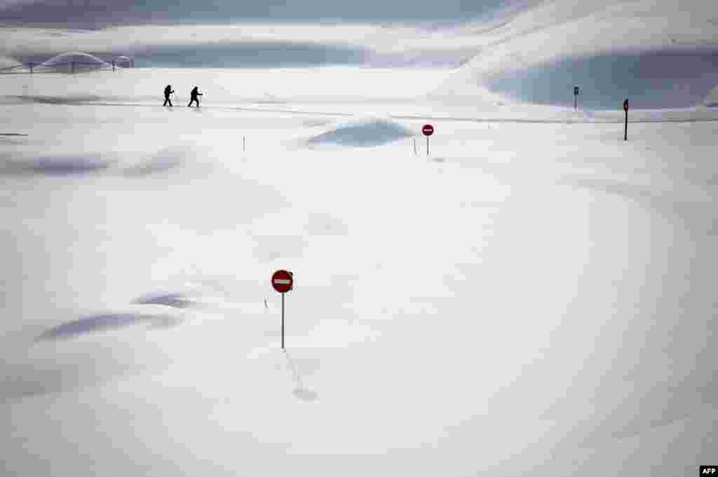 Two skiers pass by traffic signs covered in the snow by the Dappes Car Park near La Dole, Switzerland, Jan. 26, 2021.
