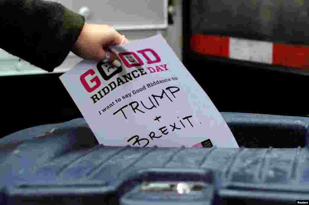 "A participant throws a piece of paper reading ""Trump and Brexit"" into a trash can to be shredded during ""Good Riddance Day"" in Times Square, New York City, Dec. 28, 2016."