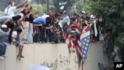 Протестующие срывают американский флаг со стены посольства США. Каир, Египт. 11 сентября 2012 года.