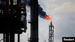 FILE - Excess natural gas is being flared, or burnt off, at a flare stack at the refinery in Tula.