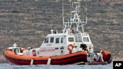 ໜ່ວຍຍາມຝັ່ງ ຂອງອີຕາລີ ກຳລັງເອົາສົບໃສ່ຖົງ ນອກເກາະ Lampedusa ວັນທີ 8 ຕຸລາ, 2013.