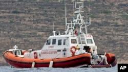 Italian Coast Guard personnel load a body bag on their patrol boat off Lampedusa island, Oct. 8, 2013.
