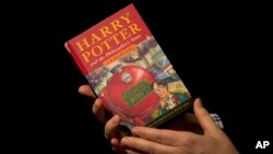 "FILE - Sotheby's director of the department of printed books and manuscripts holds a first edition copy of the first Harry Potter book ""Harry Potter and the Philosopher's Stone"" containing annotations and illustrations by author J.K. Rowling, May 20, 2013."