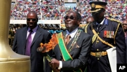 Zimbabwe's President Robert Mugabe, center, prepares to light the independence flame during Zimbabwe's 33rd independence celebrations in Harare, Apr. 18, 2013.