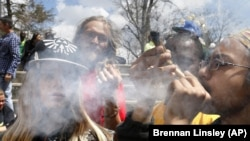 Young people listen to music and smoke marijuana during a yearly festival, in Civic Center Park in Denver, Colorado on April 18, 2015