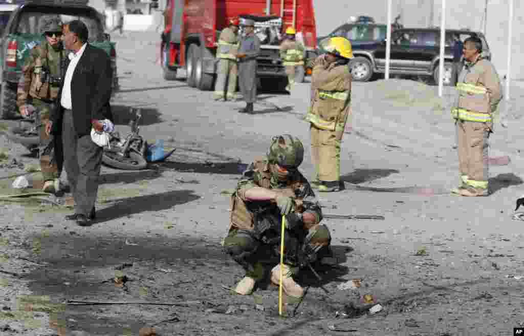 A French soldier investigates the scene of a suicide bombing that targeted a mini-bus carrying foreigners, Kabul, Afghanistan, September 18, 2012.