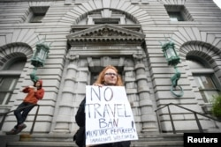 FILE - Beth Kohn protests against President Donald Trump's executive order travel ban outside the 9th U.S. Circuit Court of Appeals in San Francisco, Calif., Feb. 7, 2017.