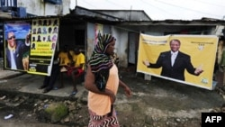 A woman walks in front a poster for Guinean presidential candidate, Alpha Conde, hung in front of the home of supporter for his party (file photo)