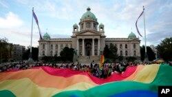 Učesnici Belgrejd prajda nose veliku zastavu duginih boja ispred zdanja Doma Narodne skupštine Republike Srbije, tokom protesne šetnje, 18. septembra 2021. (Foto: AP, Darko Vojinović)