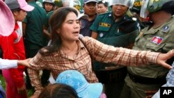 FILE - Tep Vanny of Boeung Kak Lake is blocked by riot police during a protest rally near the prime minister's residence in Phnom Penh, Cambodia, July 2, 2013.