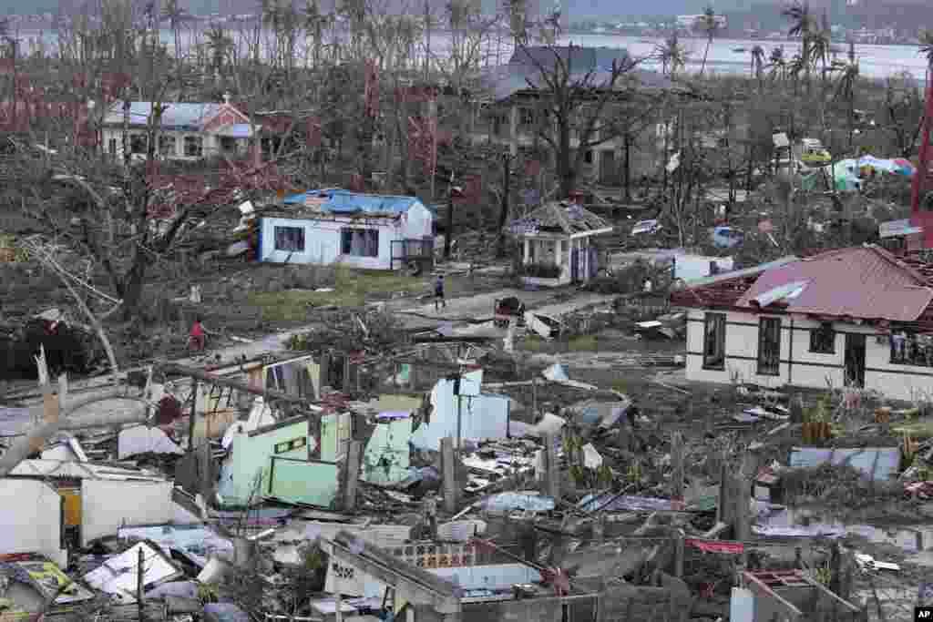 Mkazi mmoja anqatembea kando ya vifusi vya nyumba zilzioharibiwa na kimbunga kikubwa cha Haiyan katika mji wa Tacloban, jimbo la Leyte katikati ya Ufilipino.Nov. 9, 2013