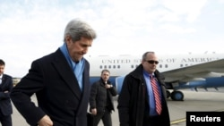 """U.S. Secretary of State John Kerry (C) steps from his plane upon his arrival in Vienna, Austria, on what is expected to be """"implementation day,"""" the day the International Atomic Energy Agency (IAEA) verified that Iran has met all conditions under the nucl"""