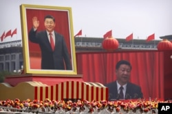 FILE - Participants cheer beneath a large portrait of Chinese President Xi Jinping during a parade to commemorate the 70th anniversary of the founding of Communist China in Beijing, Tuesday, Oct. 1, 2019.