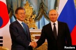 문재인 한국 대통령과 블라디미르 푸틴 러시아 대통령이 22일 모스크바 크렘린궁에서 만나 악수하고 있다.