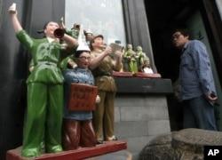 """中国陶瓷雕塑再现文革中红卫兵批斗学者的情景,学者胸前的牌子上写着""""打倒反动 学术权威"""""""