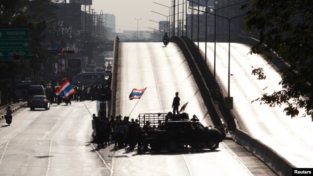 Anti-government protesters block a road in central Bangkok, January 13, 2014.