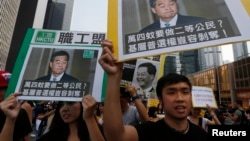 Pro-democracy protesters carrying portraits of Hong Kong Chief Executive Leung Chun-ying march to his residence in Hong Kong, Oct. 22, 2014.