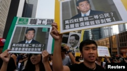 香港民主示威者舉著香港特首梁振英像和質問他的口號遊行(2014年10月22日)