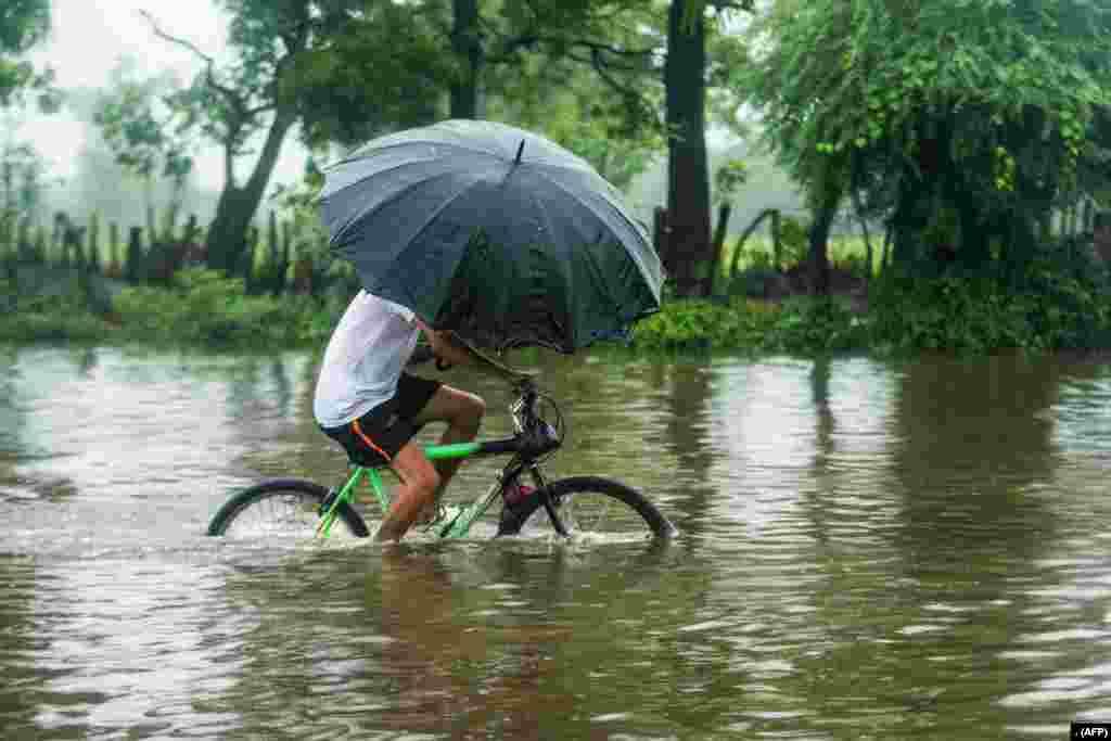 ایل سلویڈور میں شدید بارشوں سے متاثر سڑک پر ایک شخص چھتری لیے سائیکل پر اپنی منزل کی طرف جارہا ہے