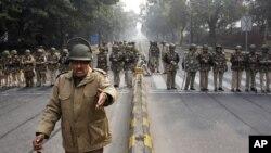 一名印度警察2012年12月24日站在新德里市中心一条公路上阻止抗议人群的警察前面对着摄像机的镜头作手势