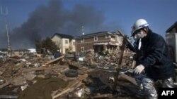 1 thi thể được phủ chăn nằm trong đống đổ nát ở một khu phố bị phá hủy trong lúc nhân viên cứu hỏa nỗ lực cứu hộ và cứu trợ ở Sendai, đông bắc Nhật Bản, 13/3/2011
