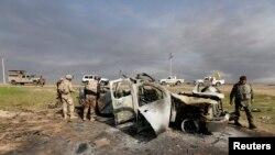 عراقی فوجی اہلکار العالم کے نواح میں موجود شدت پسندوں کی ایک تباہ شدہ گاڑی کا معائنہ کر رہے ہیں
