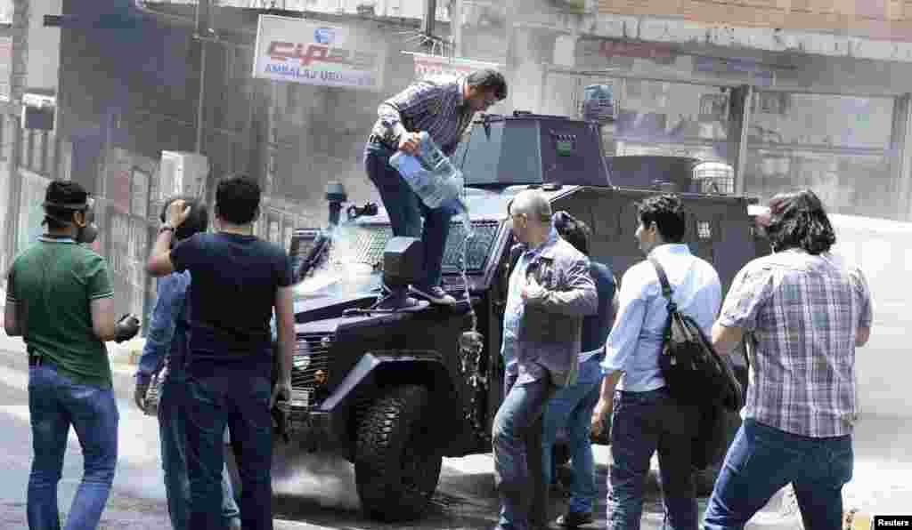Okmeydanı'nda yanan polis aracına insanlar su döküyor